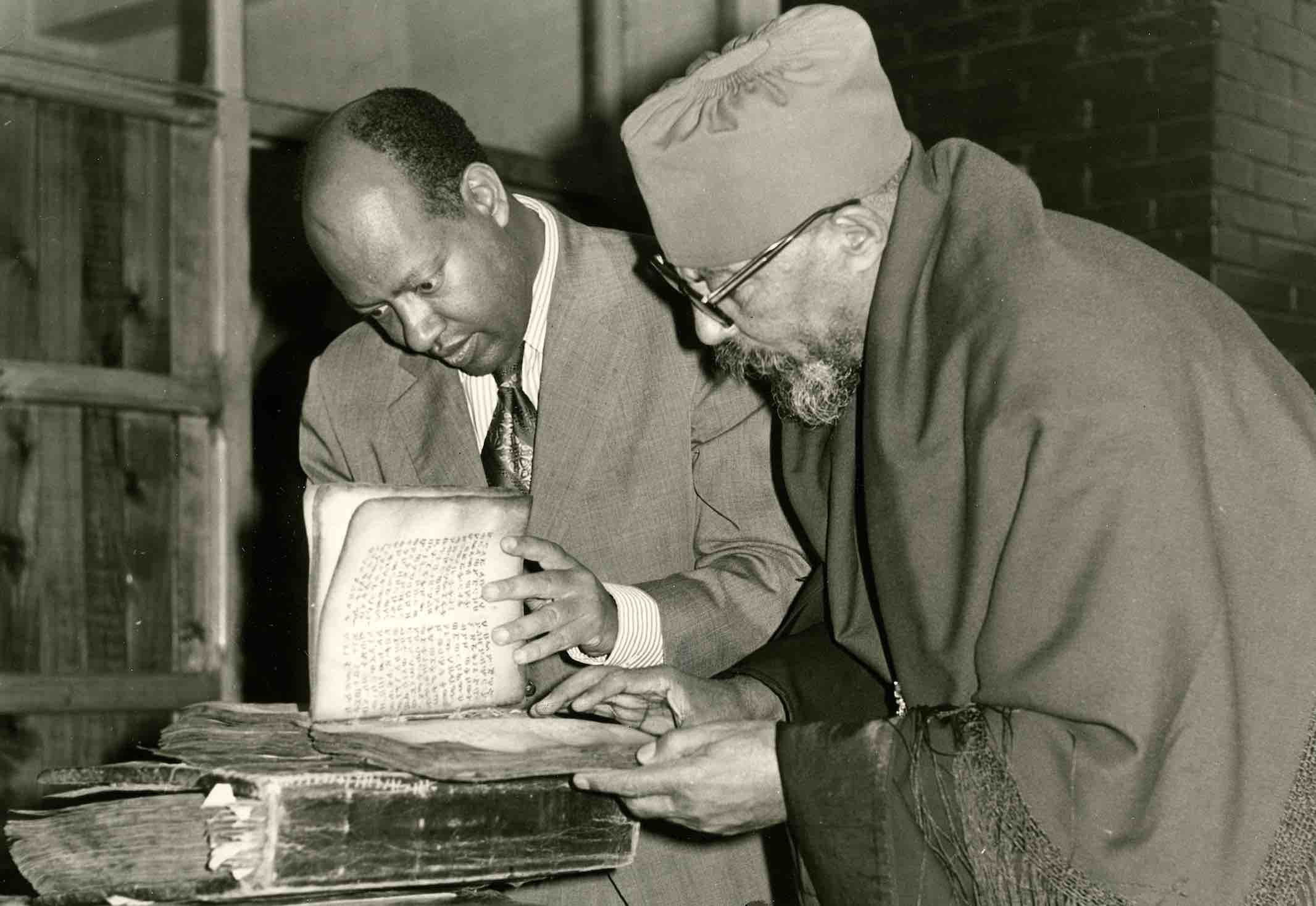 In 1974, Dr. Sergew Hable Selassie (left) shows an EMML manuscript to the patriarch of the Ethiopian church, Abuna Theophilos in Addis Ababa
