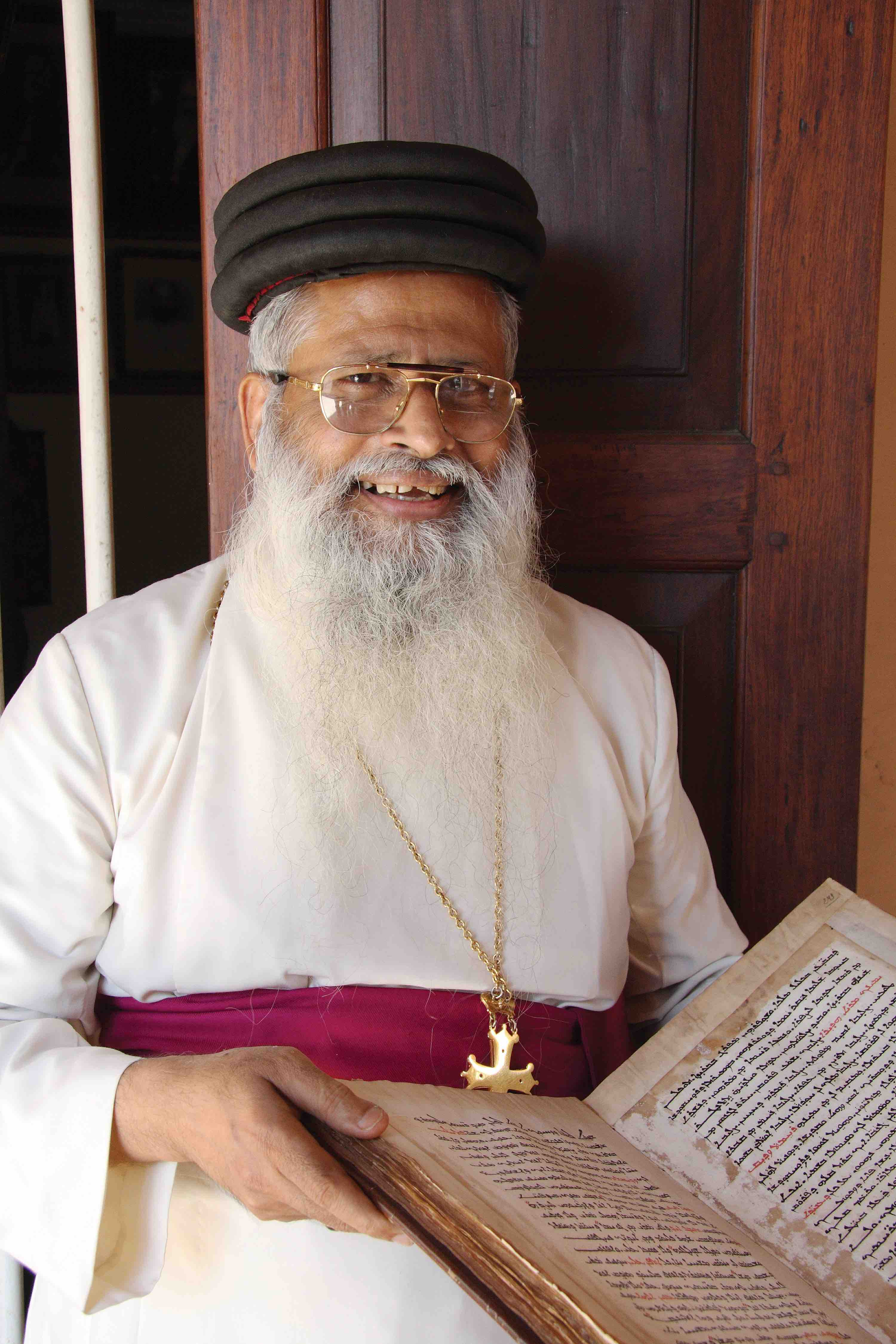 Mar Aprem Mooken, Chaldean (Assyrian Church of the East) Metropolitan of India, holding a Syriac manuscript from the collection of the Metropolitanate in Thrissur, India