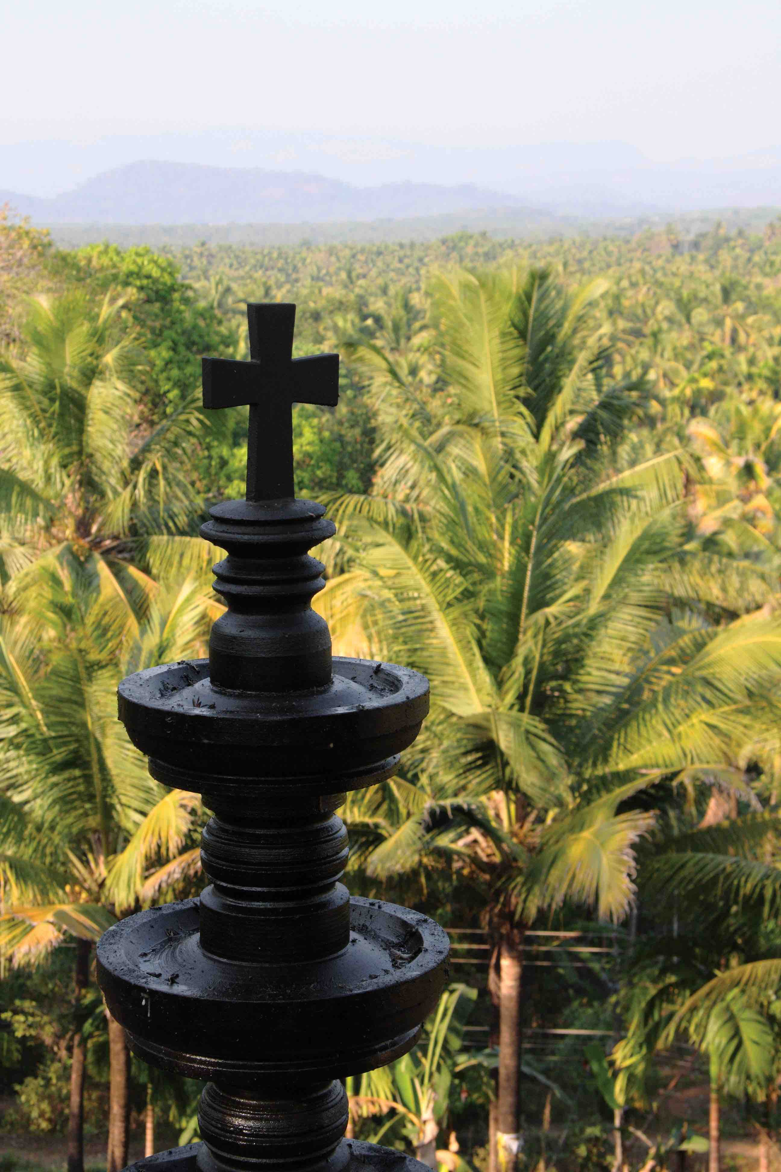 Traditional Indian stone oil lamp, topped with a cross, overlooks a coconut palm forest at the hill village of Pushpagiri